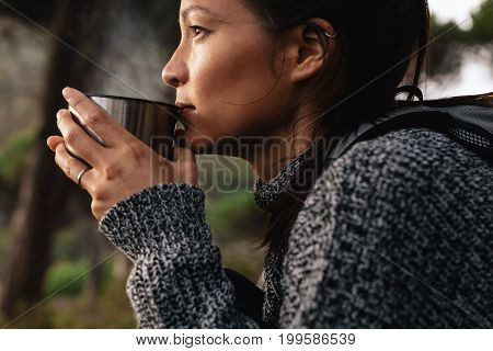 Close up side shot of young asian female hiker drinking coffee. Female hiker taking rest during hike.