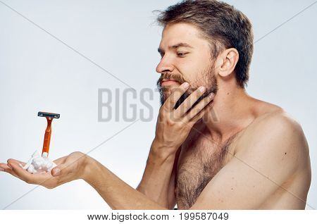 A man with a beard on a light background holds a razor and shaving foam.