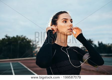 Beautiful Young Sportswoman With Earphones On Tennis Court