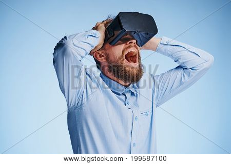 A man with a beard on a light blue background in virtual reality glasses.
