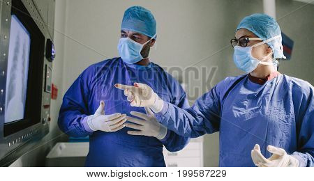 Two surgeons looking at screen and discussing while performing surgery in hospital operating room. Professional medics during surgery in operation theater.