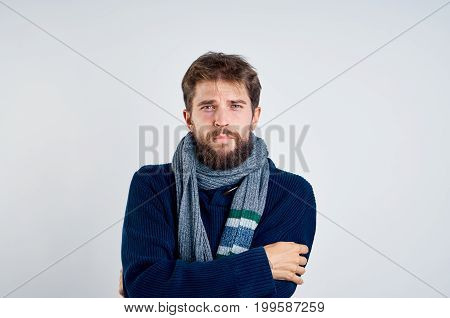 a man with a beard on a light background in a scarf and a sweater, illness, ill, sick, flu.