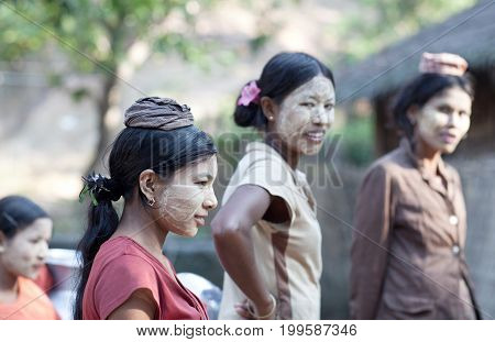 MYITKYINA, MYANMAR - JANUARY 4, 2012: Burmese women with thanaka paste on their faces going to local market. Thanaka is a yellow cosmetic paste made from ground bark.