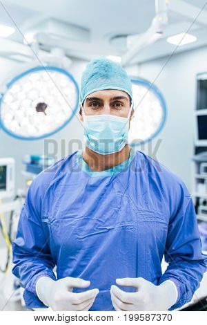 Portrait of surgeon wearing surgical gloves and scrubs in operation theater. Doctor in scrubs and medical mask in hospital operating room.
