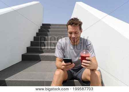Healthy smoothie drinking man using phone app on jogging break with morning red beet juice sitting on stairs outdoor.