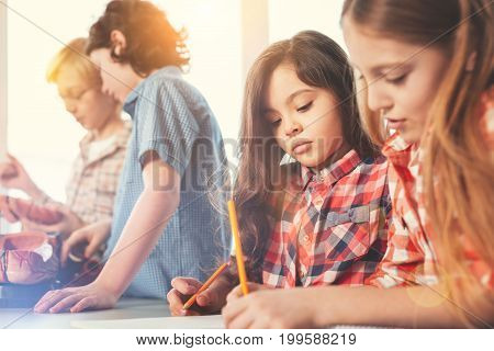 Study well. Serious pupil looking downwards while holding pencil in right hand and standing near her classmate