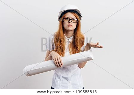 Young beautiful woman on a light background holds blueprints in a hard hat and glasses, construction.