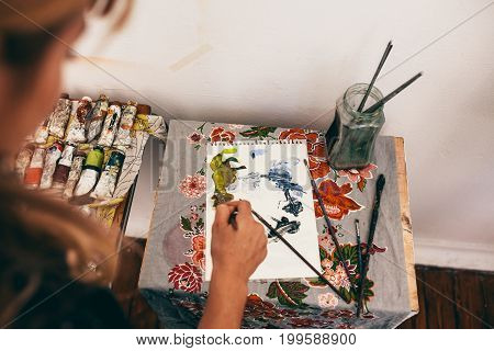 Top view of female artist painting picture on notepad. Close up of woman painter working in her workshop.