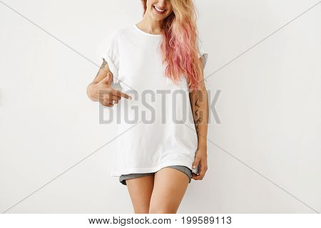 Slim Woman With Pink Hair Tips, Wearing White Loose T-shirt And Jean Shorts, Pointing At Copy Space