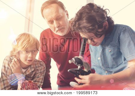 Control everything. Competent bearded teacher standing behind his pupils and wrinkling forehead while controlling their research