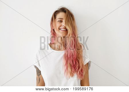 Horizontal Portrait Of Pleasant-looking Caucasian Female With Long Hair, Pink On Tips, Having Tattoo