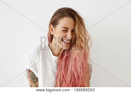 Young Female Model With Pink Hair Tips, Winking Her Eyes While Having Joy, Smiling Broadly, Feeling