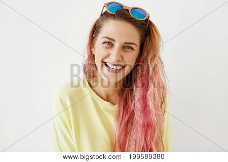 Headshot Of Attractive Young Female With Pink Hair Tips, Wearing Yellow Casual Clothes, Having Shade