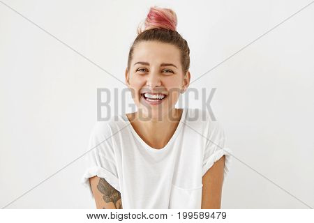 Happy Cheerful Woman Wearing Her Pinkish Hair In Bun, Looking At Camera With Joyful Expression While