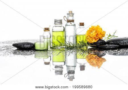 ranunculus with black stones ,oil in bottle ,fern on wet background
