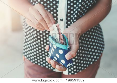 Hands holding bank bills and small money pouch