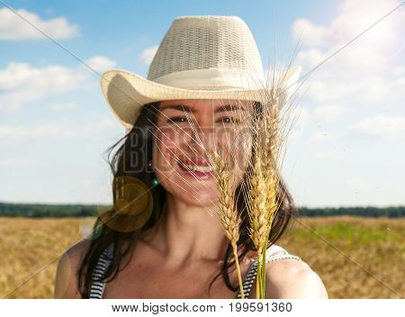 Pretty woman close up portrait. in hat in the wheat field on blue sky background. Selective focus on wheat.