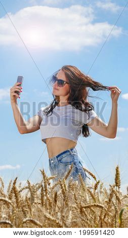 Girl in sunglasses with mobile phone on blue sky background.