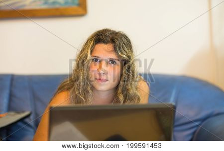 Woman working with laptop computer at night.