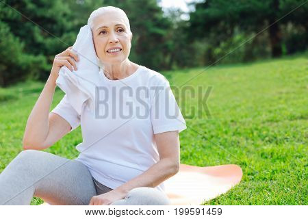 Feeling tiredness. Mature woman being deep in thoughts while sitting on the mat and wiping her face