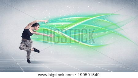 A good looking fresh street dancer dancing in front of grey background with white and bright, colorful green lines concept
