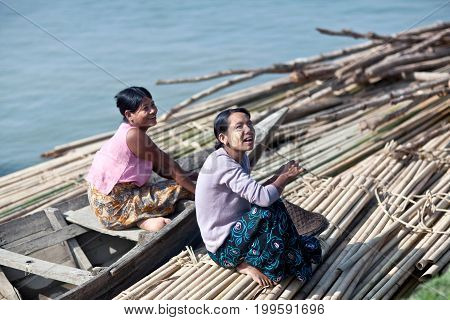 MANDALAY, MYANMAR - JANUARY 6, 2012: Smiling Burmese women traveling by wooden boat on Irrawaddy river