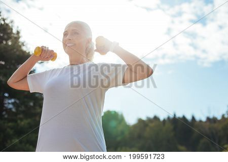 Nature inspired. Beautiful healthy female keeping arms bent in elbows while lifting dumbbells and looking forward