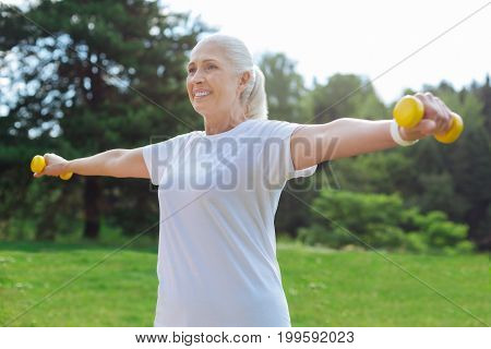 Feeling happiness. Delighted mature female keeping smile on her face and holding her equipment while standing over beautiful green background