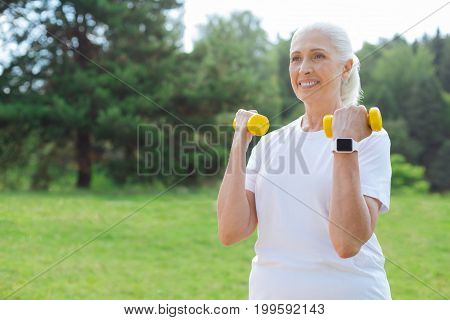 Sport on fresh air. Delighted blonde keeping smile on her face and holding dumbbells in both hands while expressing positivity