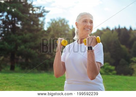 Positive thoughts. Cheerful elderly female lifting dumbbells and looking aside while keeping smile on her face