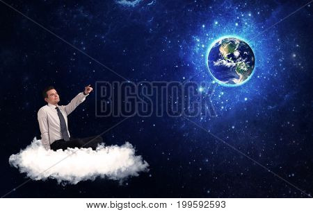 Caucasian businessman sitting on a white fluffy cloud looking and wondering at planet earth