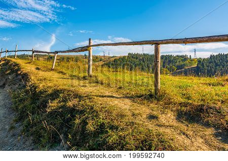 Wooden Fence Along The Path Through Countryside