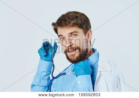 Man with a beard against a light background, medicine, stethoscope, doctor, portrait.