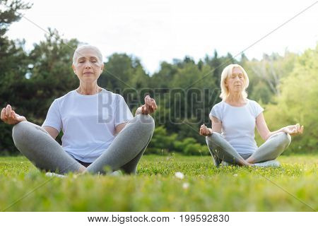 Feel the moment. Concentrated elderly women sitting on the grass and keeping eyes closed while putting hands on knees