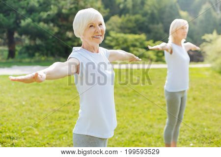 Friendly atmosphere. Healthy female person keeping smile on her face and standing in semi position while raising her arms