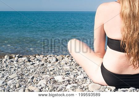 The Girl Sits On The Seashore In The Weakening Pose