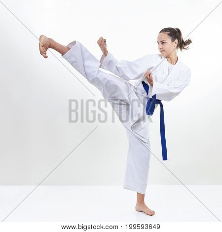 A girl with a blue belt beats kick leg