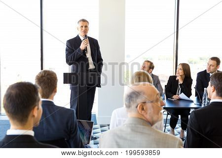 Business speaker with microphone in front of audience conference seminar concept