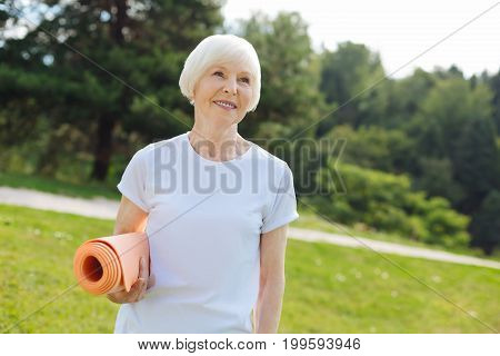 Happy female. Positive delighted sportswoman keeping smile on her face and looking upwards while enjoying nature