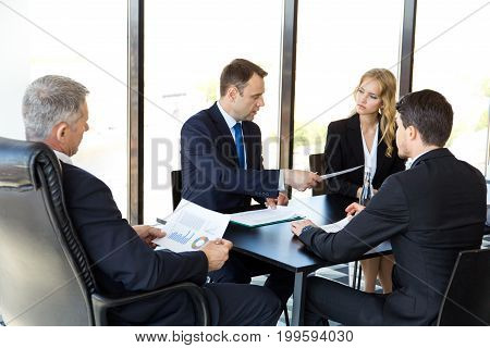 Serious business people work with graphs and diagrams at meeting at office table