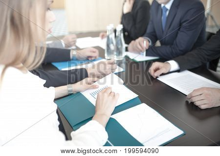 Business people discussing documents at workplace in office sitting around the table