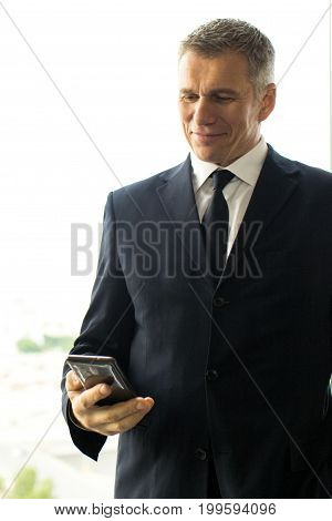 Mature businessman using smartphone standing near office window with view of city