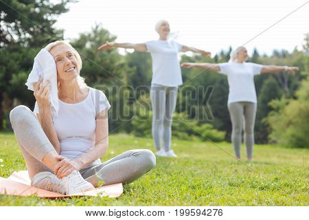 My friends. Delighted mature female keeping smile on her face and siting on the mat while wiping her forehead