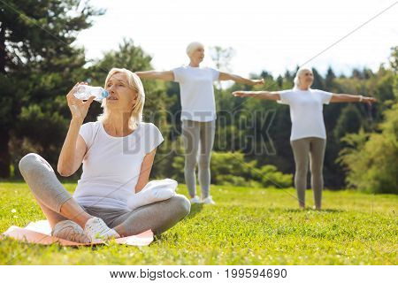 Renew your breath. Tired woman sitting in yoga pose while leaning on the mat and looking upwards