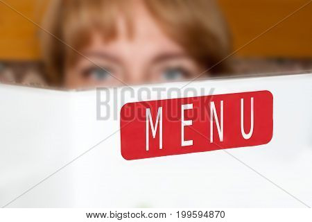 The Beautiful Girl Holds The Menu In Hand
