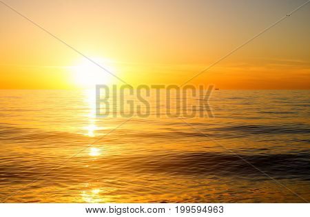 the sun to set over the horizon reflected in the sea