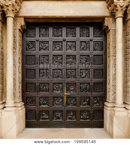 entry door of the protestant Grossmunster church (The Great Minster Cathedral) in Zurich, Switzerland, with religious and symbolic carvings over the whole door