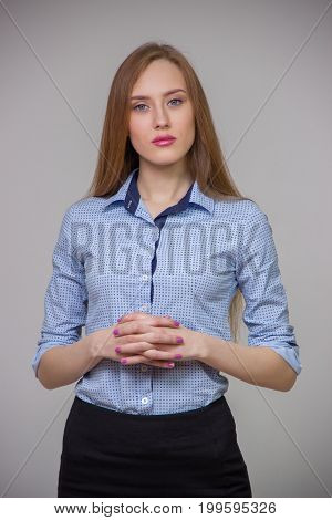 Young beautiful business woman in a blue shirt stands with her arms crossed and with other gestures and thinks over a gray background