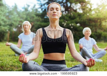 Believe in yourself. Healthy women being serious while sitting in yoga poses and keeping eyes closed