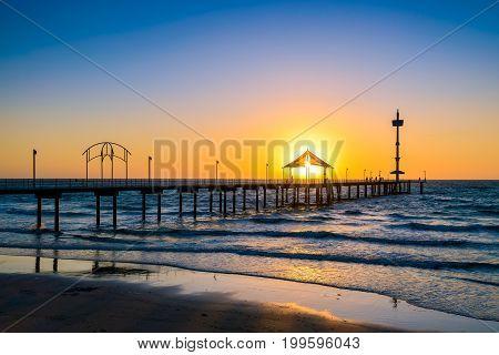 People walking along Brighton Beach jetty at sunset South Australia